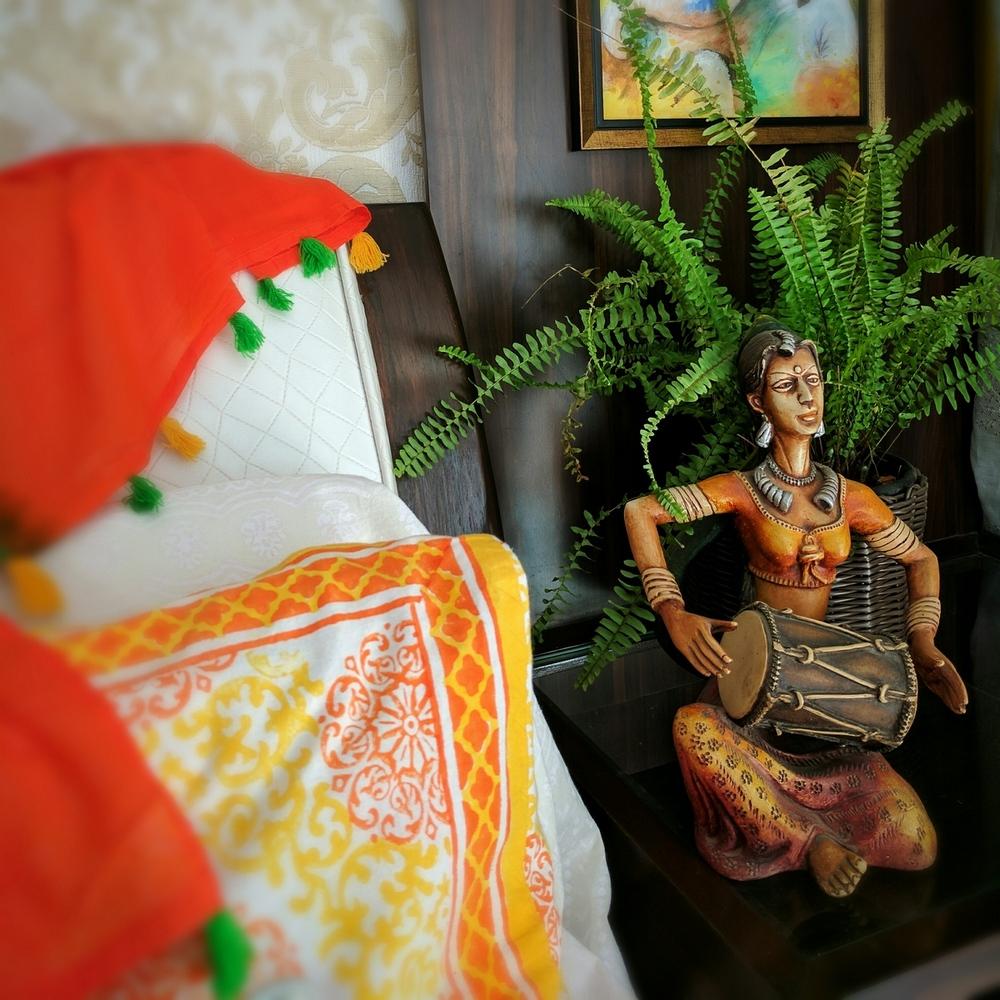 ब्लॉक प्रिंटेड कुशन कवर और एक संगीतकार की मूर्ति घर को भारतीय रूप देगी।