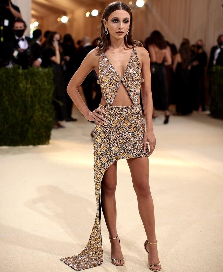 Emma Chamberlain ने गोल्डन कलर की मिनी ड्रेस पहनी जिस पर मिरर का वर्क किया गया है।