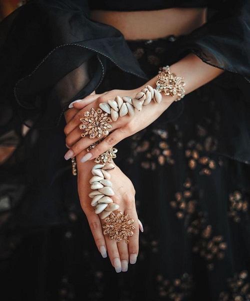 हल्दी या संगीत में Sea Shell से तैयार हाथ फूल ट्राई कर सकती है।