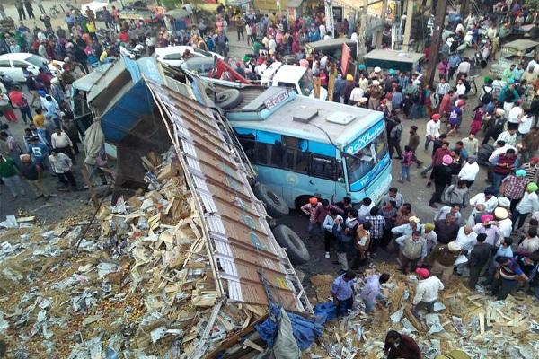 पुल से नीचे बस पर गिरा ट्रक, बाल-बाल बचे यात्री
