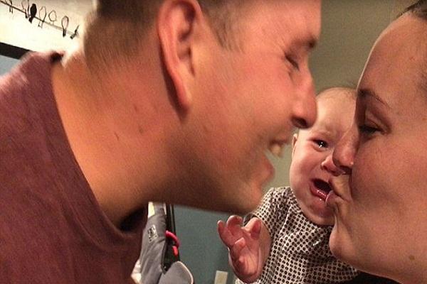 jealous baby girl bursting tears when her parents kiss