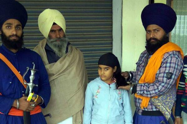 cutting the hair of a sikh student