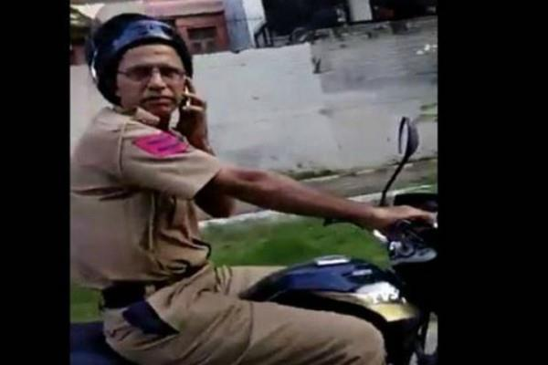 the policeman was driving the bike while talking on the phone