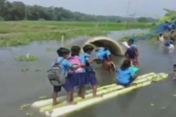 students of a primary school cross a river on banana stems