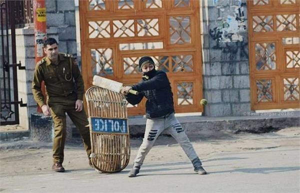 kashmiri boy playing cricket with police cop