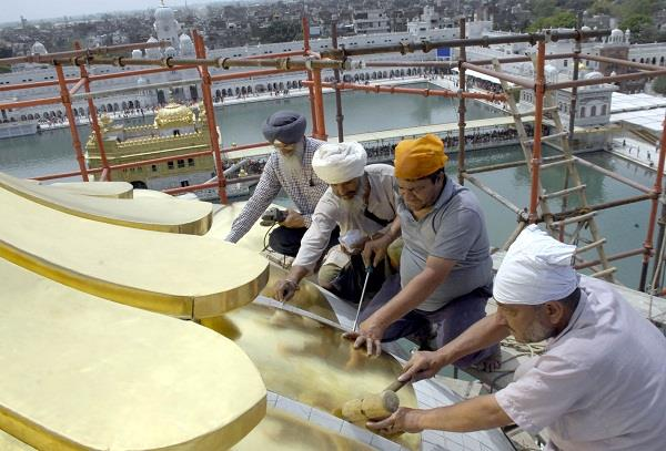 putting gold plate on the dome of the holy shrine of shri harimandir sahib