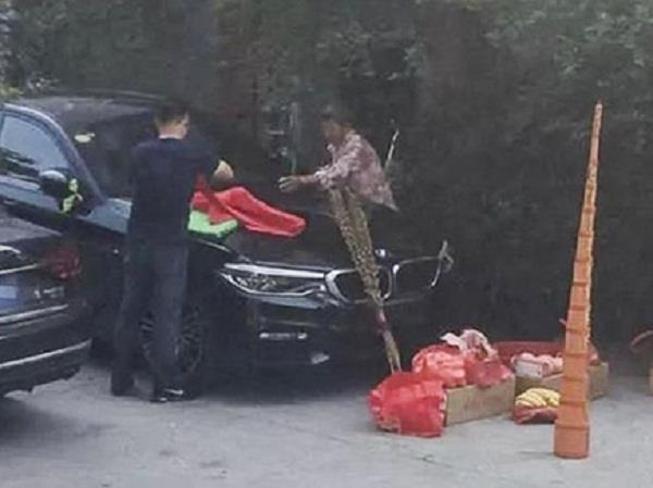 chinese man lights incense sticks near new bmw burns luxury car