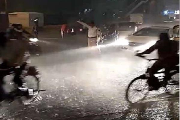 constable carrying traffic control in heavy rain