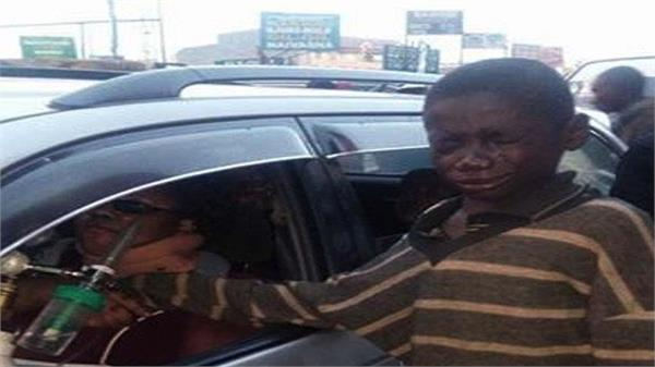 homeless boy approaches car to beg for change until he peeks inside