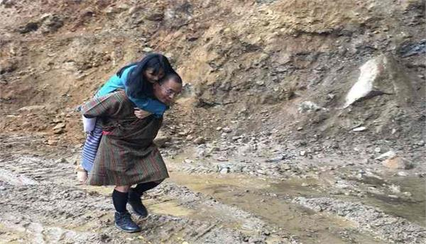 ex pm of bhutan walked in a mud puddle road carrying his wife