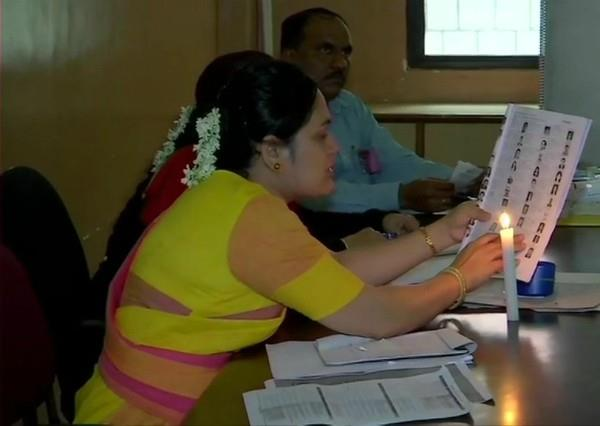 polling booth powered off people vote with the help of candles