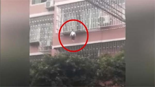 video girl dangles from third floor balcony trapped by neck