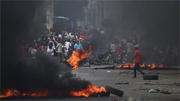 protesters and police clash in haiti inmates escape from prison