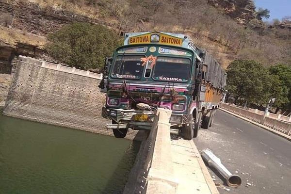 truck hanging up to 20 feet on the bridge