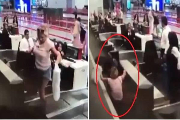 first time flyer checks herself in with luggage on conveyor belt