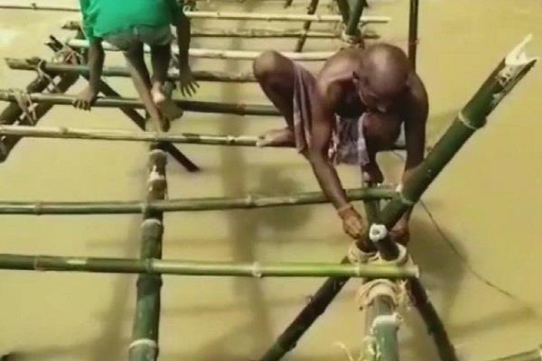 villagers build temporary bamboo bridge