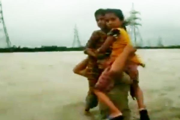 sitting on the shoulders of constables two children were taken out of the flood