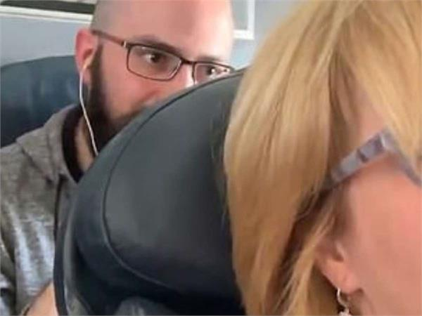 man punching woman s reclined seat continuously in american airlines