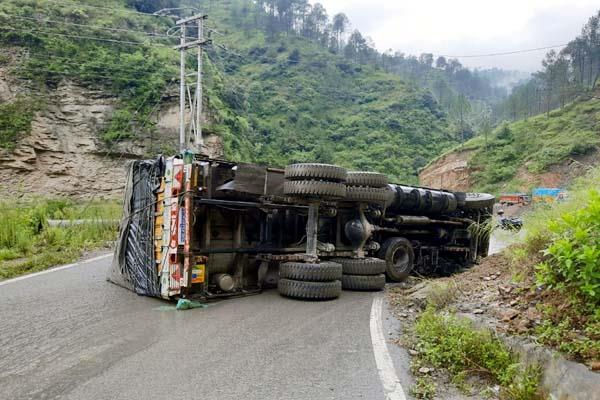 सड़क के बीचोंबीच पलटा सेब से लदा ट्रक,चालक ने ट्रक से छलांग लगाकर बचाई जान