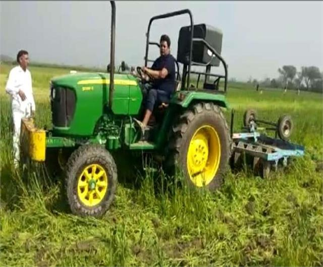 farmer runs tractor on wheat crop