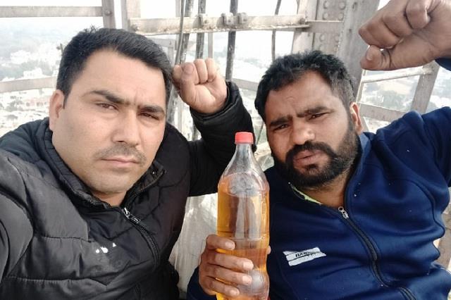 two unemployed ett tet passes on tower carrying petrol bottle